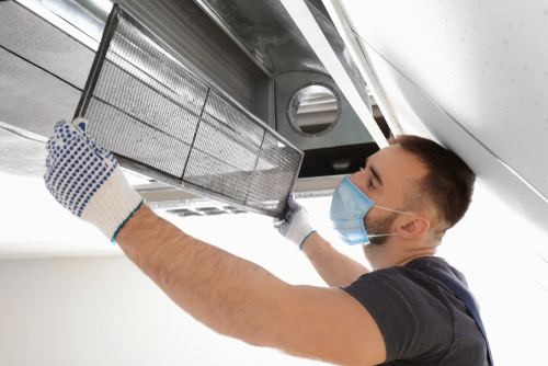 male-technician-cleaning-industrial-air-conditioner-indoors