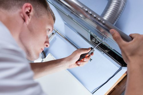 handyman fixing a kitchen extractor